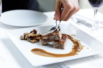 Apuesto joven sirviendo pan de carne en un plato en el restaurante.