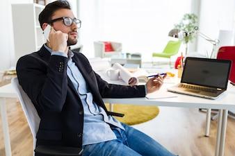 Apuesto joven utilizando su teléfono móvil en la oficina.
