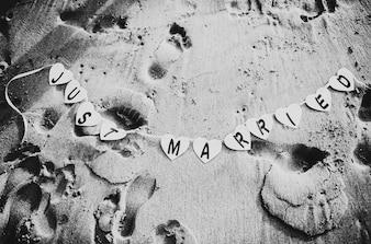 Arena de la playa con un cartel de recién casados
