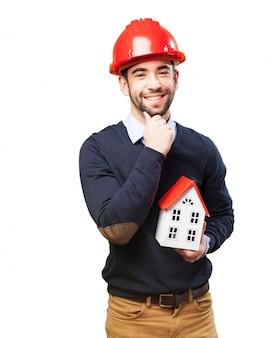 Arquitecto feliz tocándose la barbilla mientras sujeta su proyecto
