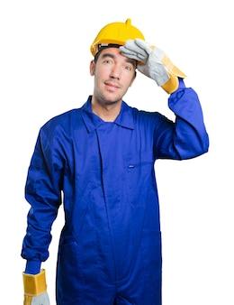 Asombrado trabajador con gesto de búsqueda sobre fondo blanco