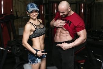 Athletic pareja - hombre y mujer muestra sus músculos
