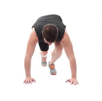 Atleta con las manos en el suelo preparado para correr