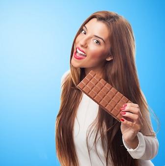 Atractiva morena con la barra de chocolate.