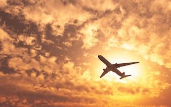 Avión pasando por el sol en un dia nublado