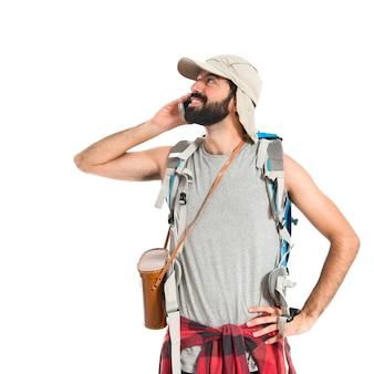 Backpacker hablando con móvil sobre fondo blanco