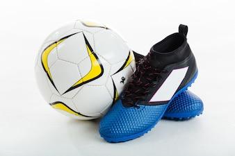 Balón de fútbol junto a unas botas
