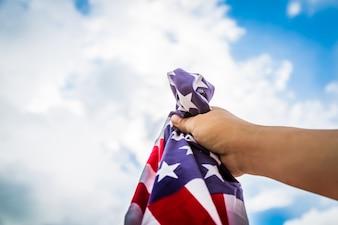Bandera americana sujetada por una mano con nubes de fondo