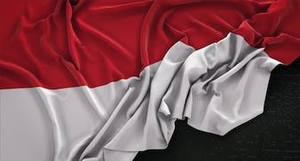 Bandera de Indonesia arrugado sobre fondo oscuro 3D Render