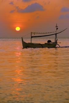 Barco pescando al anochecer
