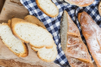 Barras de pan cortadas en rodajas sobre un mantel de tela a cuadros