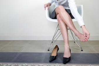 Bastante Empresaria sentado en una silla de masaje de su pie