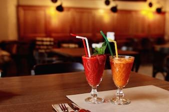Batidos de color rojo y naranja sobre una mesa