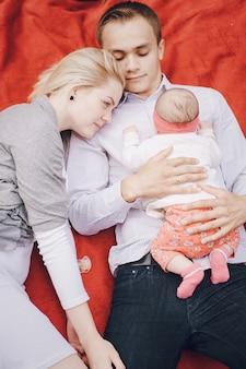 Bebé tumbado encima del padre mientras su madre los mira