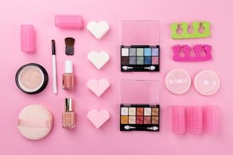 Belleza Spa Concepto Femenino. Diferentes Maquillaje Cosméticos Essentials Cuidado de la belleza en el Plano Lay Fondo Rosa. Vista superior. Encima.