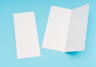 Bifold plantilla de papel blanco sobre fondo azul.