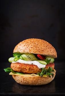 Big sandwich - hamburguesa con jugoso hamburguesa de pollo, queso, pepino, chile y salsa tártara sobre fondo negro