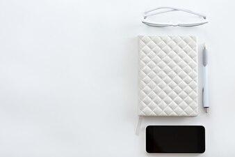 Blanco escritorio de oficina con gafas, teléfono móvil y lápiz