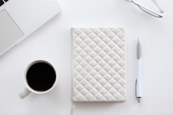 Blanco escritorio de oficina con una parte de la computadora portátil, vasos, café