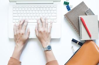 Blanco mesa de escritorio con la empresaria usando la computadora portátil y beber café