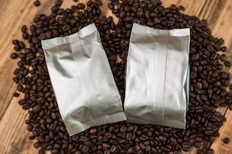 Bolsas de café con granos de café alrededor