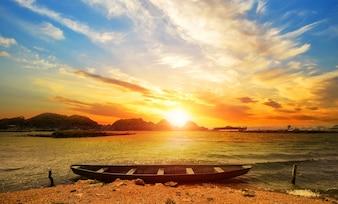 Bonito paisaje de playa al atardecer con una barca