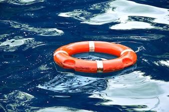 Bote salvavidas rojo en agua azul.