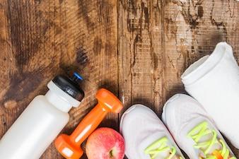 Botella de agua con zapatillas deportivas y pesas y una manzana