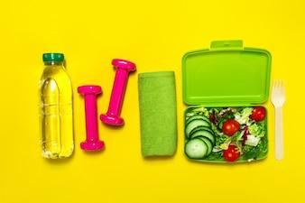 Botella de agua y pesas junto a una ensalada