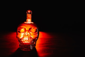 Botella de cristal del cráneo en oscuridad