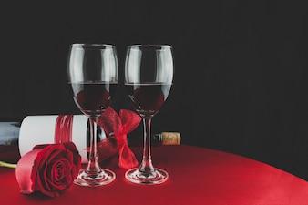 Botella de vino con dos copas y una rosa encima de una mesa