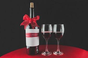 Botella de vino con un lazo rojo y dos copas con vino