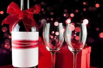 Botella de vino con un lazo rojo y dos copas vacías con efecto bokeh