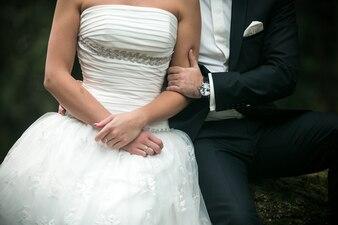Brazo de hombre agarrando el brazo de una mujer con vestido de novia
