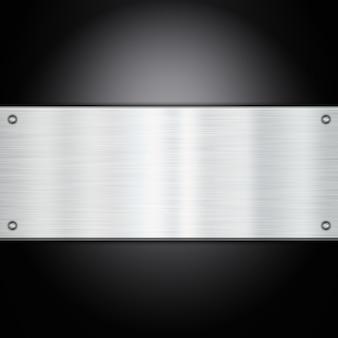 Brillante placa de metal sobre un fondo de fibra de carbono