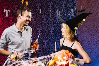 Bruja y chico charlando en la fiesta de Halloween