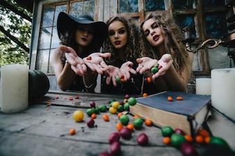 Brujas diabólicas lanzando caramelos