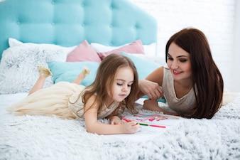 Brunette mujer mira a su hija pintura algo mientras descansan en la cama grande
