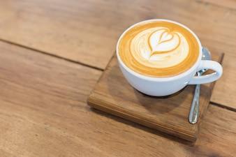 Café caliente de Latte del arte en la tabla.