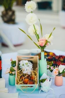 Caja con flores y una botella florero