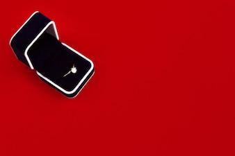 Caja negra de anillo de pedida en una mesa roja