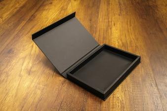 Caja negra de madera abierta en el suelo