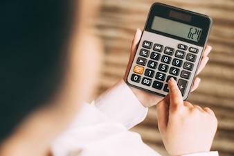 Calculadora calcular joven que controla botón