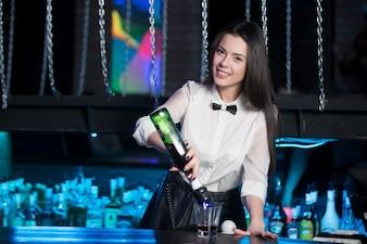 Camarera sonriendo preparando una copa