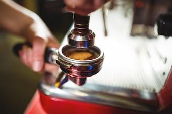 Camarera utilizando un pisón para presionar café molido en un portafiltro