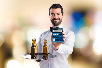 Camarero con botellas de cerveza en la bandeja de la celebración de una calculadora sobre fondo desenfocado