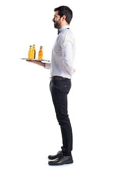 Camarero con botellas de cerveza en la bandeja