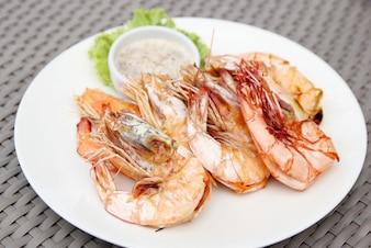 Camarones a la parrilla con salsa de mariscos en plato blanco