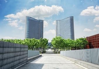 Camino con árboles hacia dos edificios simétrico