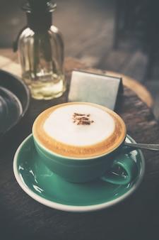 Cappuccino caliente en la taza de café verde en la mesa de madera en el café. estilo del efecto del filtro del tono del color de la vendimia.